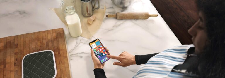Mulher usando um iPhone na cozinha