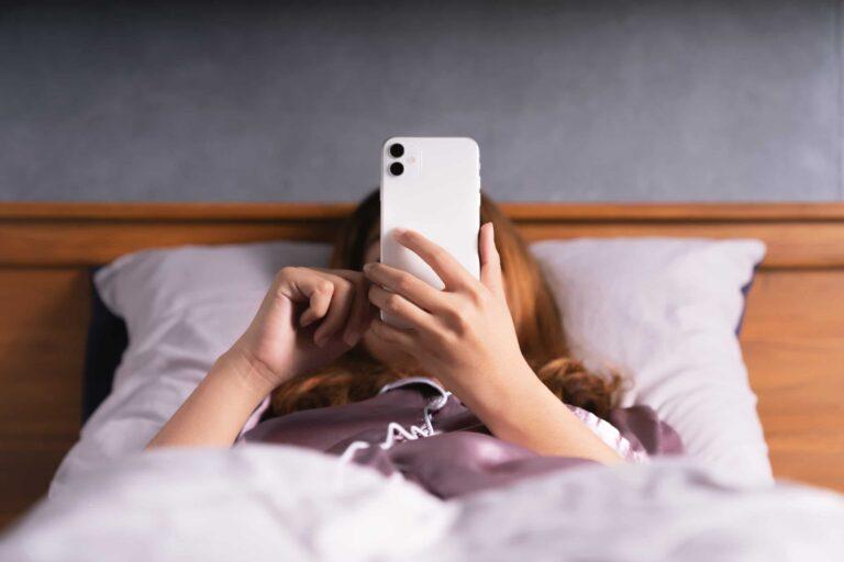 Mulher usando o iPhone na cama